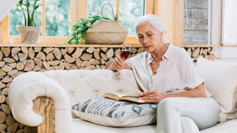 Senior woman sitting on sofa holding wine glass reading book