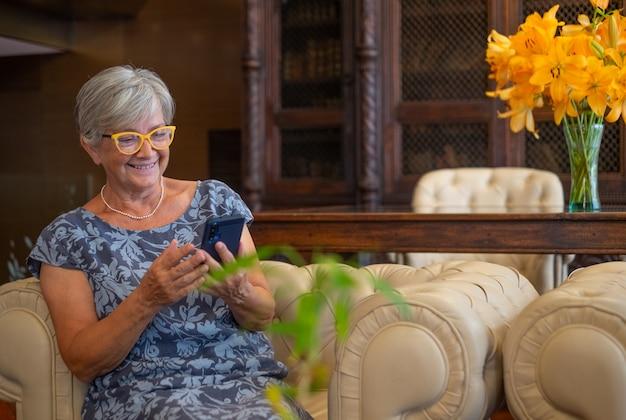 휴대 전화를 사용하여 소파에 앉아있는 노인 여성, 편안한 순간을 즐기는 웃는 현대 퇴직자