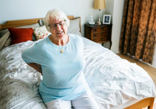 痛みでベッドに座っている年配の女性