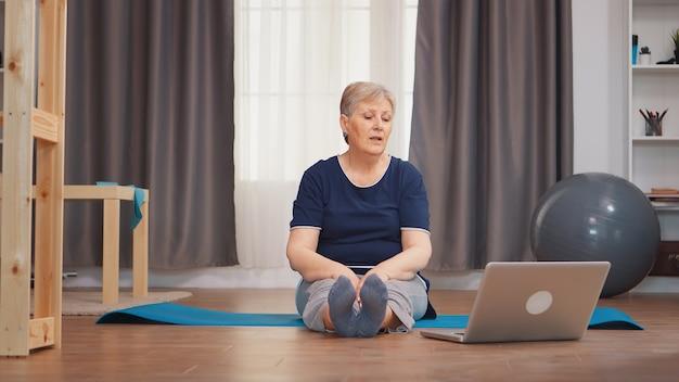 マットの上に座っている男の子を伸ばすヨガマットの上に座っている年配の女性。オンライン学習と研究、アクティブな健康的なライフスタイルスポーティな老人トレーニングトレーニングホームウェルネスと屋内運動