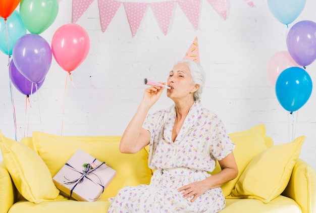 Senior woman sitting on sofa blowing party horn