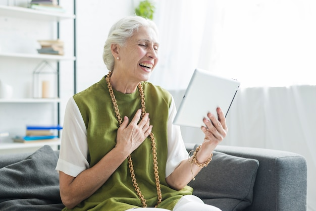Senior woman sitting on sofa looking at digital tablet laughing