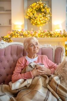 Senior woman sitting on a sofa and looking nostalgic