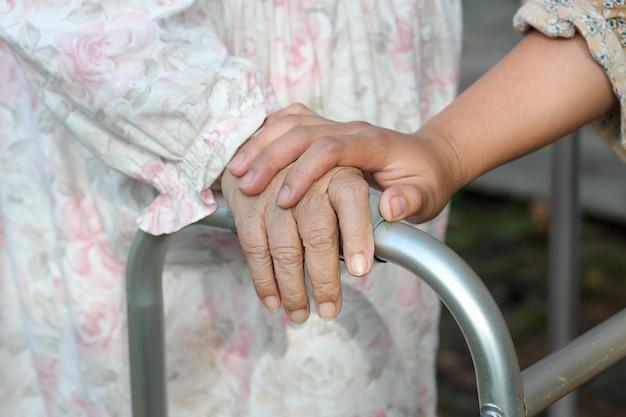 座っている年配の女性は介護者と歩行器を使用します