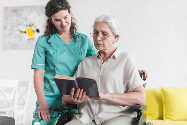 Senior woman sitting on wheelchair reading book with nurse standing behind