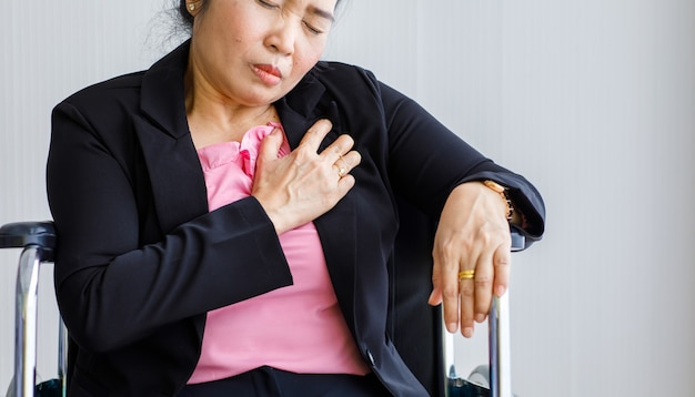 Senior woman sitting on wheelchair suffering from sudden heart attack and hold chest. concept of emergency health care and affected from  cardiopulmonary resuscitation, heart problem.
