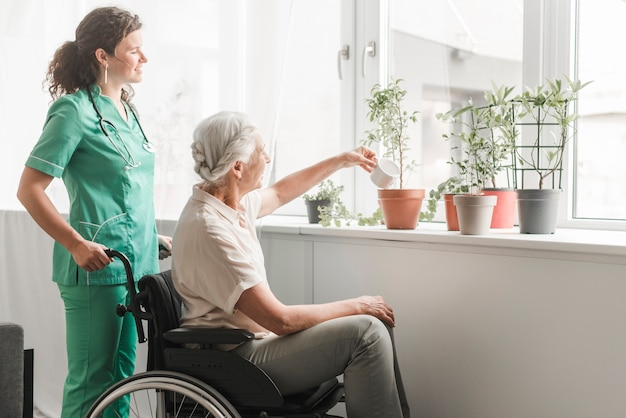 Senior woman sitting on wheelchair watering plants with nurse standing behind