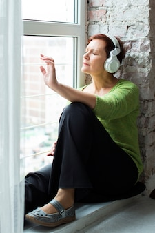 Senior woman sitting next to a window and listening music