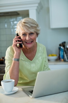 고위 여자 노트북에 앉아 및 휴대 전화 통화
