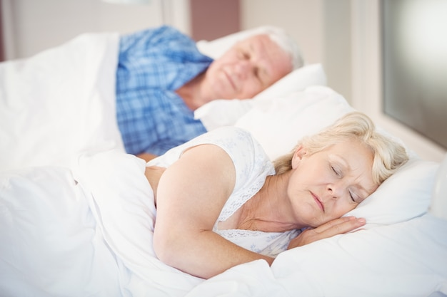 Senior woman sleeping besides husband on bed