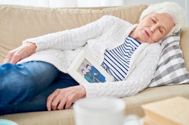 Пожилая женщина спит на диване