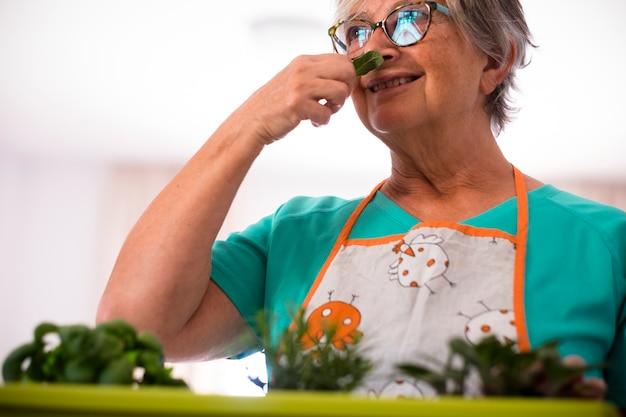 屋内で植物の匂いを嗅ぐ年配の女性-引退し、屋外で眼鏡をかけて成熟した女性が自分の製品や植物をチェックしている-白人女性の植栽