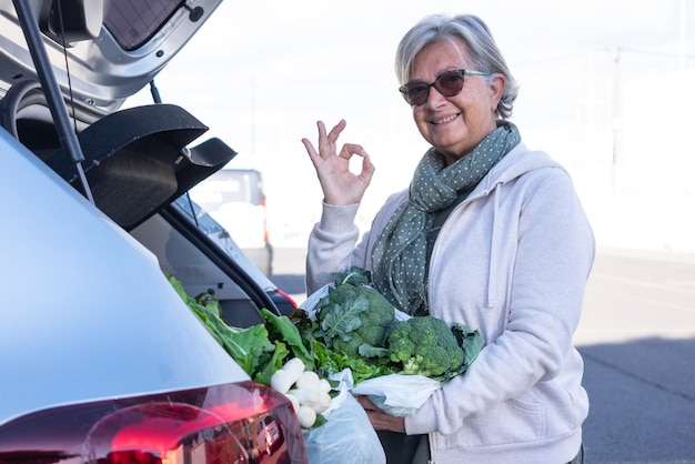 Senior woman smiles after shopping for fresh vegetables by putting them in the car trunk. positive sign with hand for an healthy eating