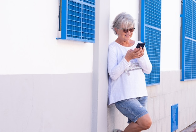 Senior woman smiles reading message on her smartphone. standing against a white wall using wireless technology. joyful elderly lifestyle