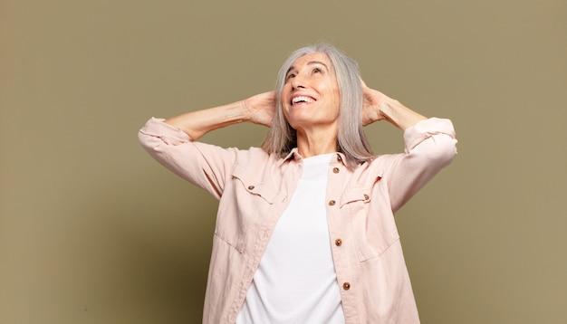 年配の女性は笑顔でリラックスし、満足し、のんきで、前向きに笑い、身も凍るように感じます