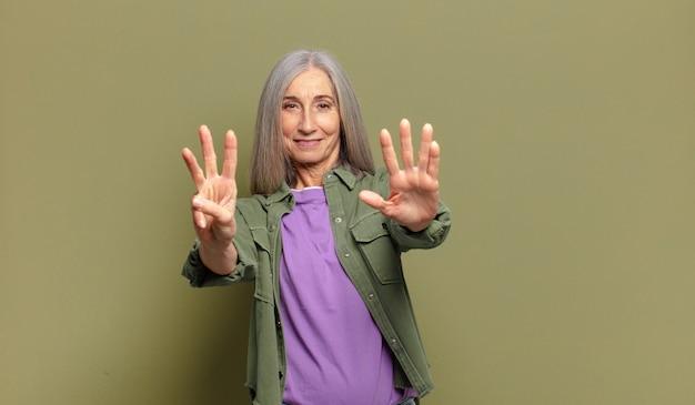 수석 여자 웃 고 친절 하 게 찾고, 앞으로 손으로 번호 8 또는 여덟 번째를 보여주는 카운트 다운