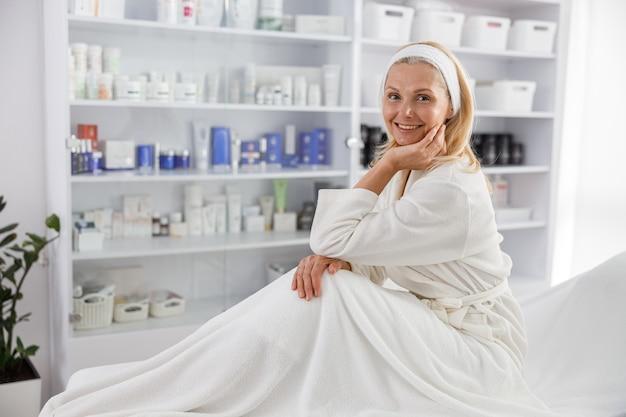 Старшая женщина улыбается и ждет косметической процедуры в клинике эстетической косметологии.