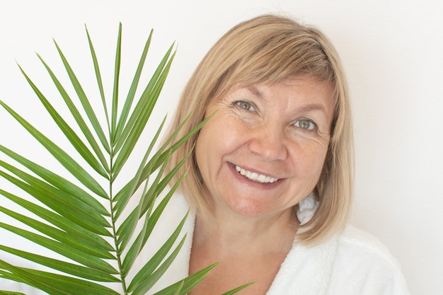 Senior woman smiling anti-age concept with palm leaf. mature woma face after spa treatment. old age in joy, plastic surgery clinic, cutie grandmother, cosmetology, new senior, pensioner, mature people
