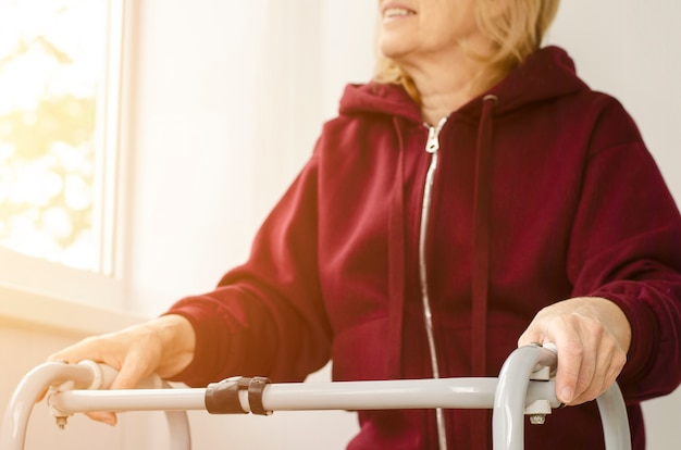 Senior woman smiling and sitting, looking at the window with her hands on the handles of a walker.