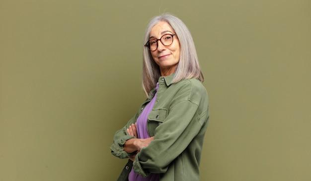 Старшая женщина улыбается камере со скрещенными руками и счастливым, уверенным, довольным выражением лица, боковой вид