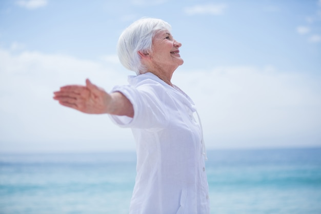 Senior woman smiling while exercising at beach