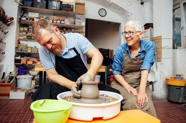 年配の女性が陶芸教室の先生と一緒にホイールに粘土を回転