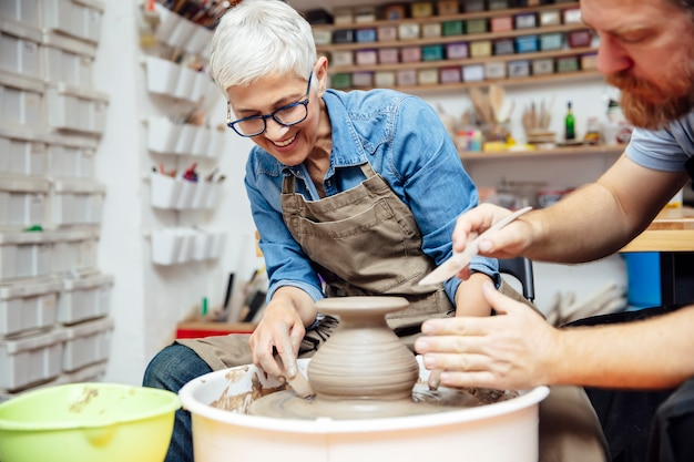 Senior woman spinning clay on a wheel with teacher at pottery class