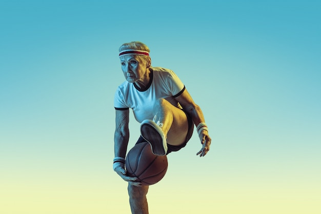 Senior woman in sportwear playing basketball on gradient background, neon light. female model in great shape stays active. concept of sport, activity, movement, wellbeing, confidence. copyspace.
