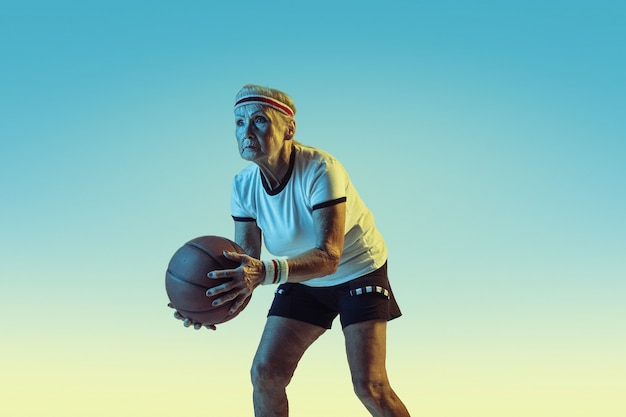 Senior woman in sportwear playing basketball on gradient background, neon light.