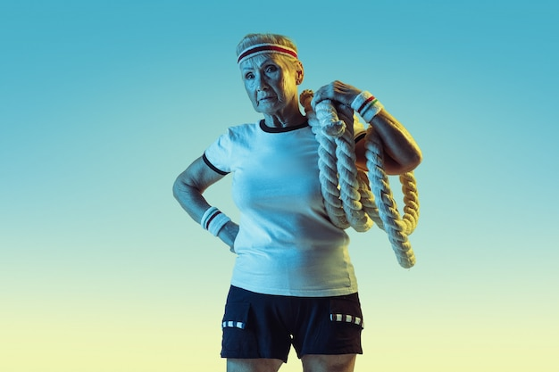 Senior woman in sportwear training with ropes on gradient background, neon light.