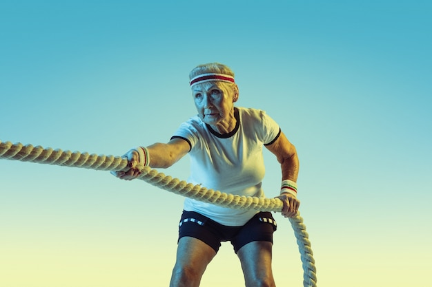 Senior woman in sportwear training with ropes on gradient