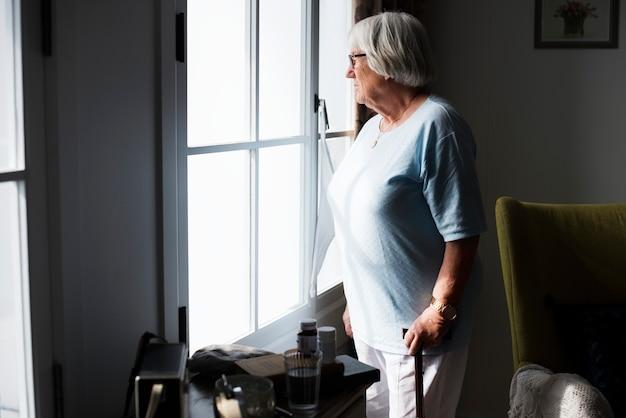 집에서 혼자 서있는 고위 여자