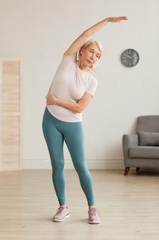 立って自宅の部屋で朝の練習をしている年配の女性