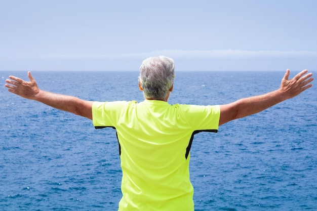 Senior woman standing at the beach with open arms, looking at the horizon over water