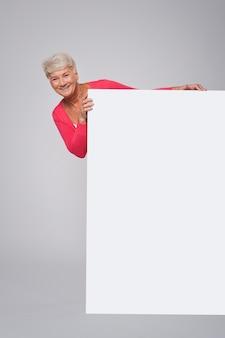 Старшая женщина, стоящая за белым рекламным щитом