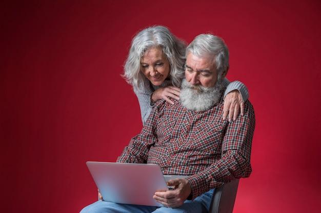 Donna senior che sta dietro il suo uomo che si siede sulla sedia che esamina computer portatile contro il fondo rosso