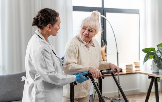 Старшая женщина, стоящая в помещении рядом с врачом