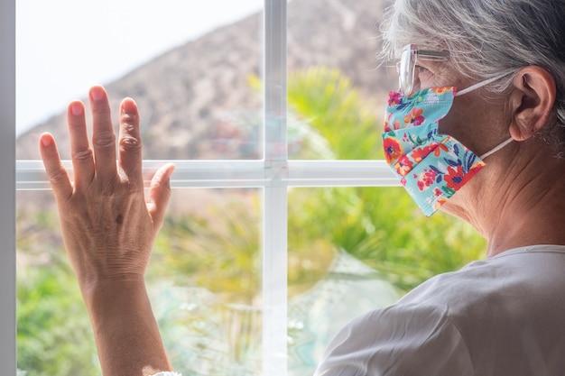 年配の女性は、外を見て、covid検疫のために窓に家にいます