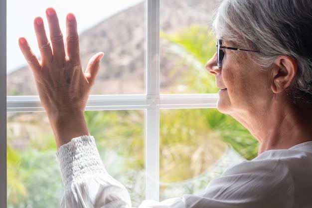 밖을 내다보는 창가에서 집에 있는 노인 여성