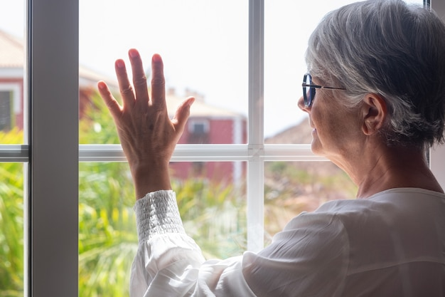 Senior woman stay home at the window looking out