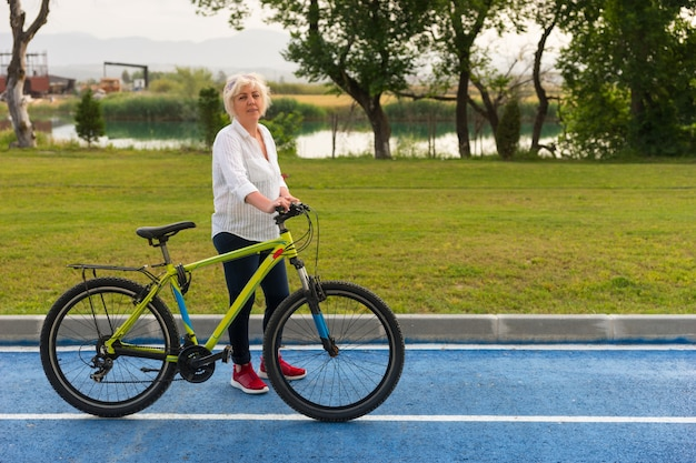 Senior woman stood with bicycle on track, park and lake in background.