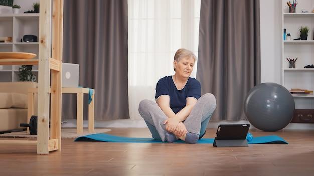 ヨガマットの上に座ってオンラインレッスンを見ながら体を伸ばす年配の女性。オンライン学習と研究、アクティブで健康的なライフスタイルのスポーティな老人トレーニングトレーニングホームウェルネスと屋内運動