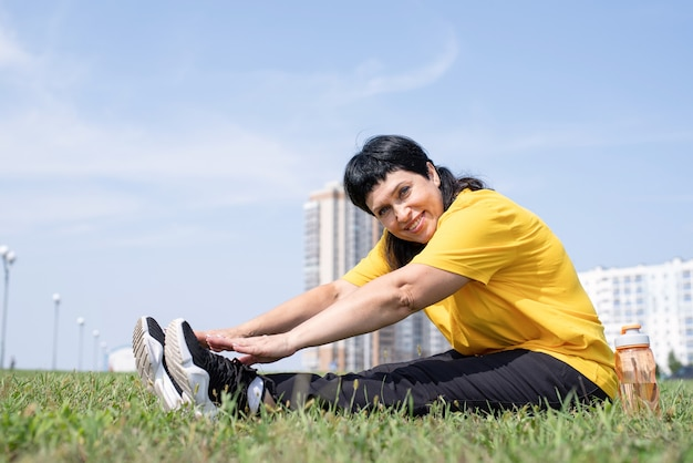 Senior woman stretching her legs on grass in the park