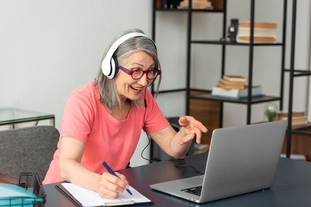 노트북을 사용하고 메모를하는 동안 집에서 공부하는 고위 여자