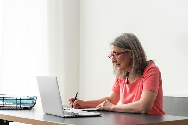 Старшая женщина учится дома, используя ноутбук и делая заметки