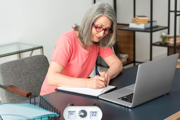 Senior woman studying at home while using laptop and taking notes