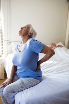 Старшая женщина страдает от боли в спине в спальне дома