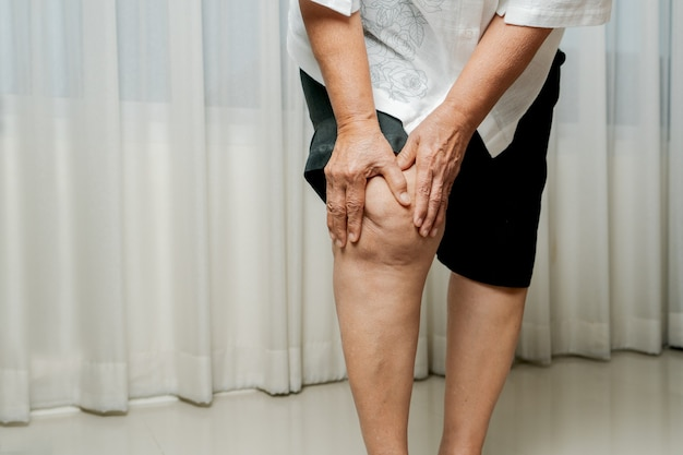 自宅で膝の痛みに苦しんでいる年配の女性、健康問題の概念