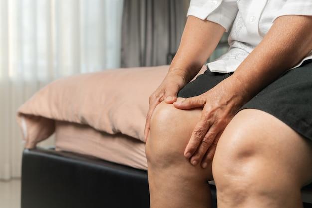 집에서 무릎 통증으로 고통받는 고위 여자, 건강 문제 개념