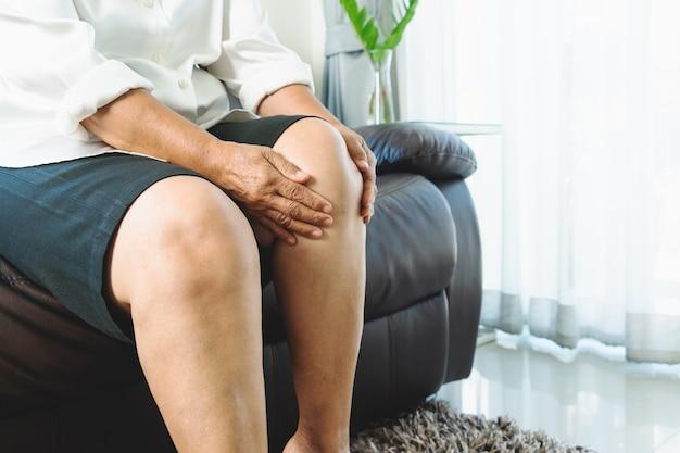 집에서 무릎 통증으로 고통받는 노인 여성, 건강 문제 개념